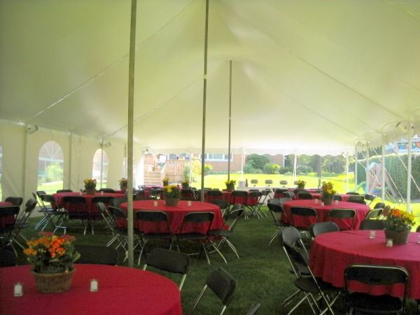 Black folding chairs and tables with red tablecloths under tent Chair Rental - Chicago, 60064